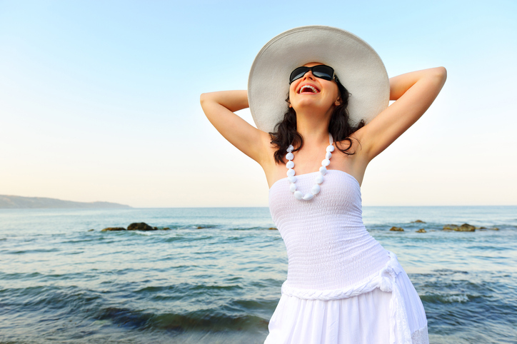 Woman laughing against an ocean backdrop
